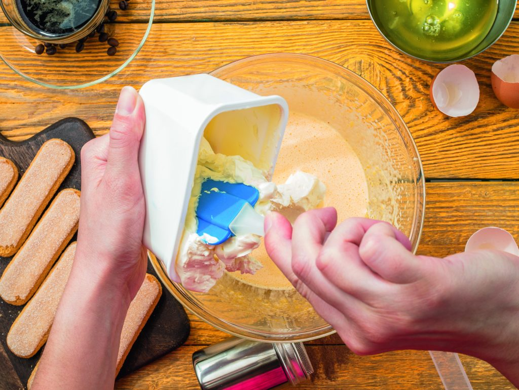Photo of cook with trowel preparing tiramisu. Table with biscuits, cheese, eggshell
