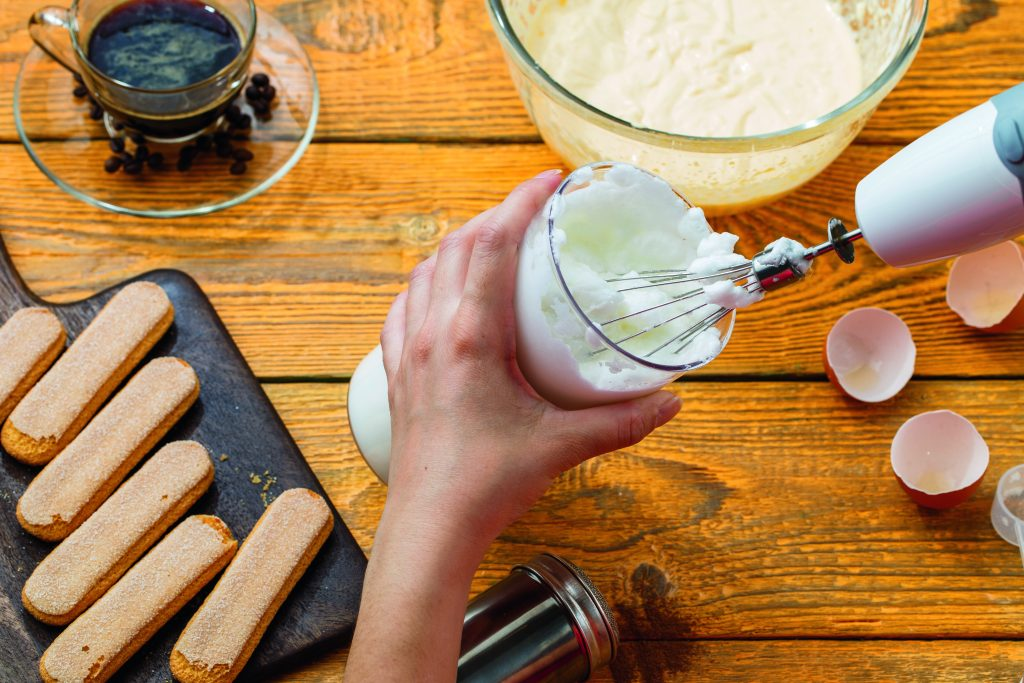 Image of cooking tiramisu, human hands with whisk, cookies, coffee, cups, cheese on wooden table